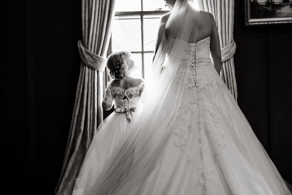 Bride & Flower girl looking out window